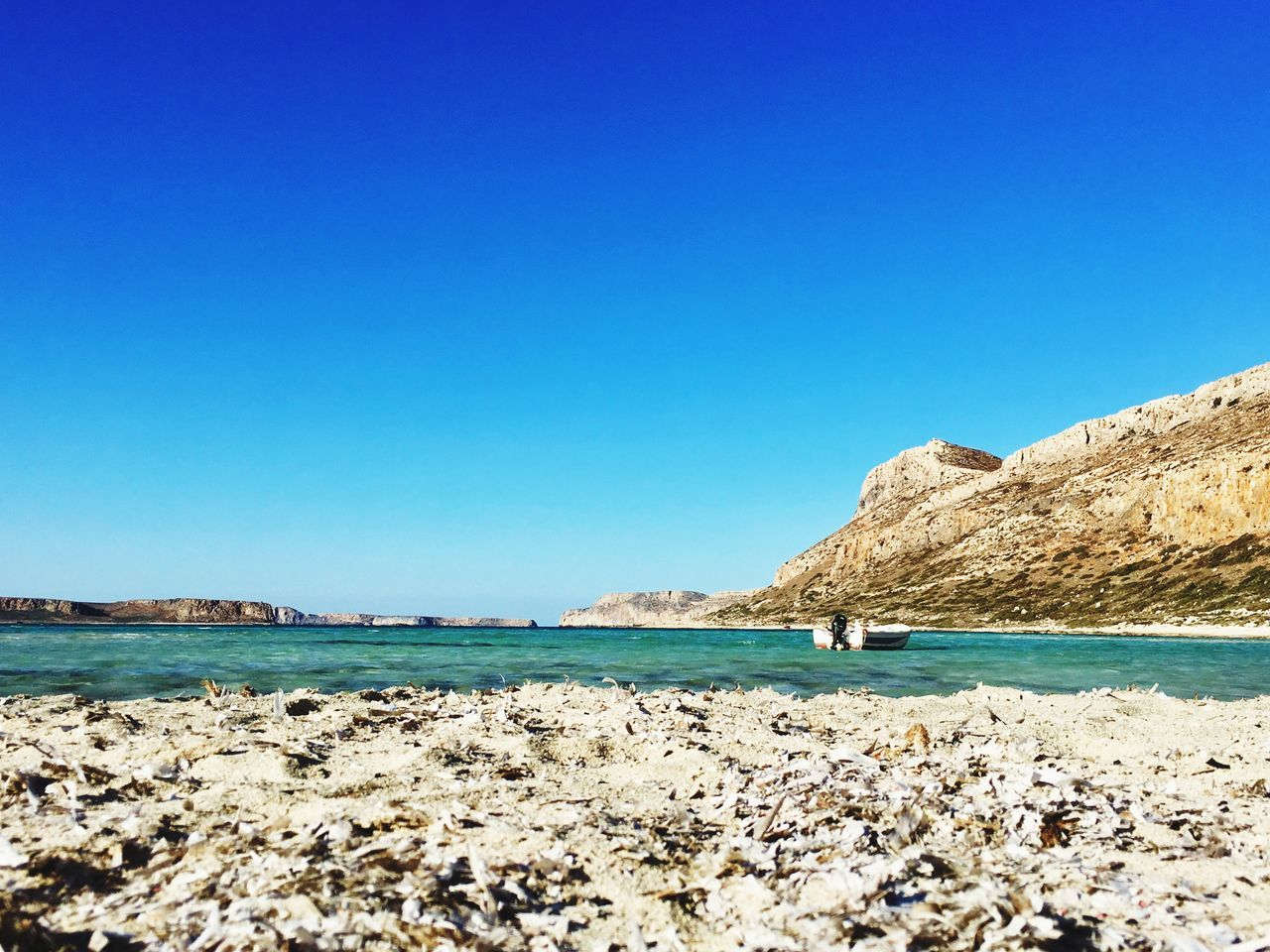 water, sea, sky, clear sky, blue, copy space, beauty in nature, scenics - nature, land, rock, nature, solid, day, tranquil scene, tranquility, beach, rock - object, idyllic, rock formation, outdoors