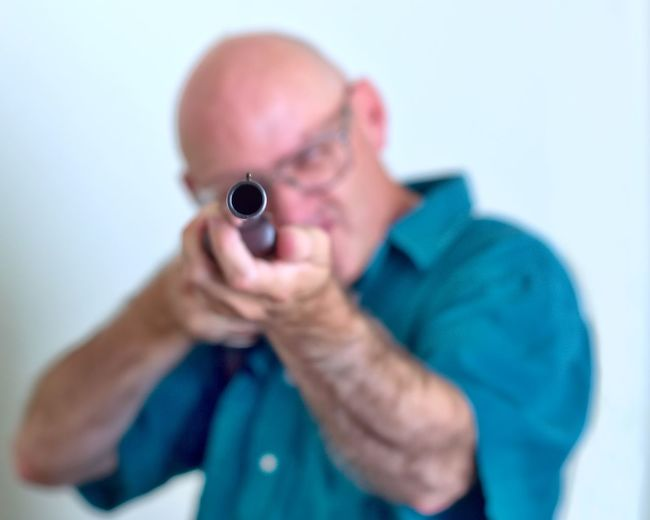Close-Up Of Man Shooting With Rifle Against White Background