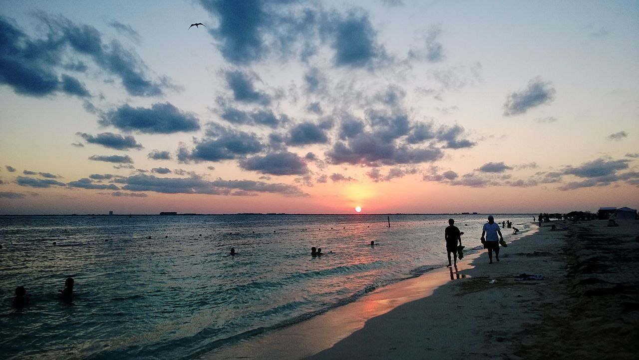 sea, sunset, beach, beauty in nature, water, nature, scenics, shore, sky, horizon over water, sand, tranquil scene, walking, tranquility, cloud - sky, leisure activity, real people, silhouette, outdoors, lifestyles, togetherness, vacations, men, full length, day, people