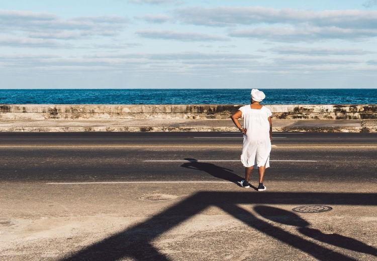 Full length rear view of man walking on beach