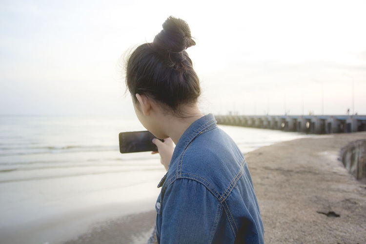 Woman Photographing Sea Through Mobile Phone At Beach