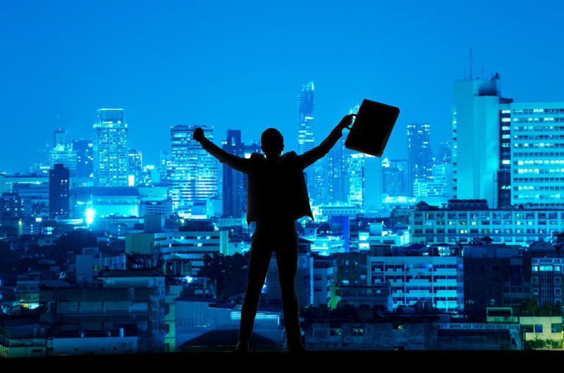 Rear View Of Man Standing Against Illuminated Cityscape