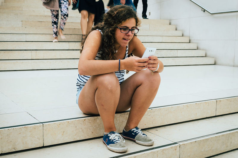 Young Woman Using Phone While Sitting On Steps