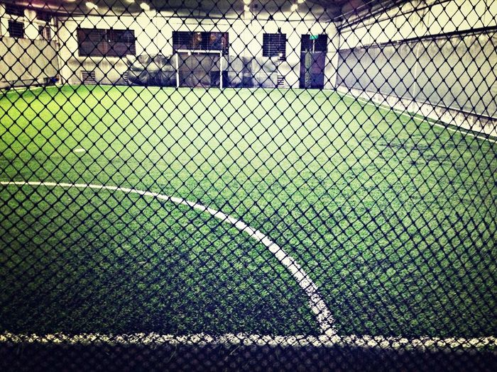 View of football pitch through wire mesh fence