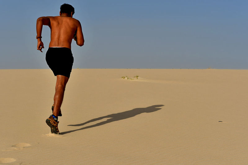 Full length of shirtless young man running on sand at desert during sunny day