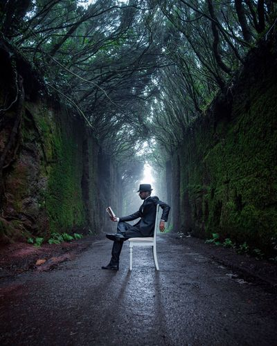 Man Sitting On Road Amidst Trees