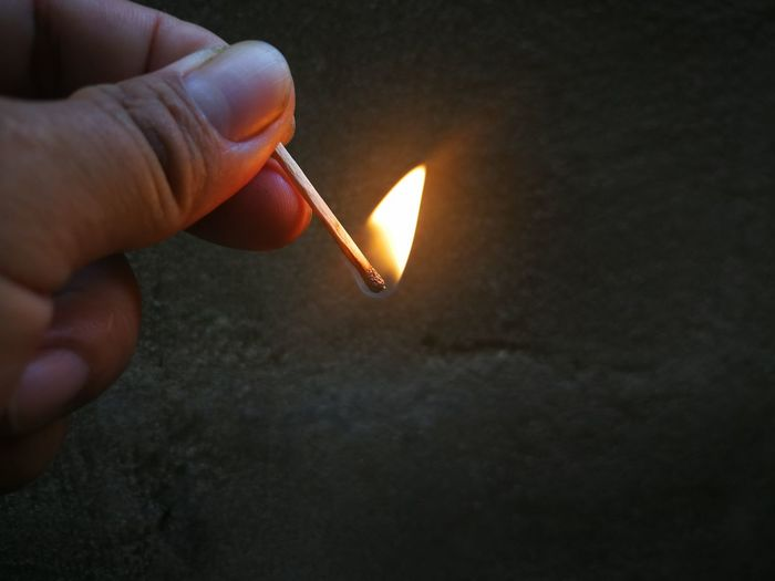 Close-up of cropped hand holding matchstick