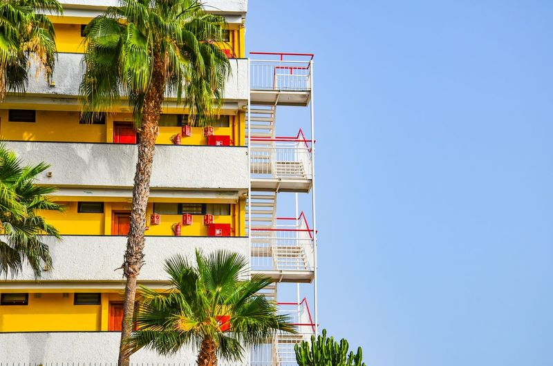 Holiday Feelings Architecture Building Exterior Clear Sky Built Structure Balcony Outdoors Tree Day Low Angle View Blue No People Palm Tree Plant Growth Nature Sky Stairs Yellow Red Holiday Playa Del Ingles Emergency Stairs Paint The Town Yellow Fresh On Market 2017 The Graphic City The Architect - 2018 EyeEm Awards