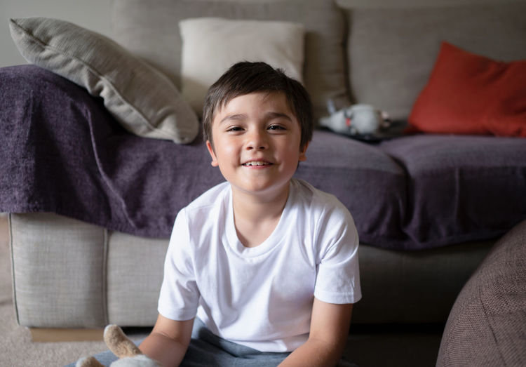 Portrait of smiling boy sitting on sofa at home