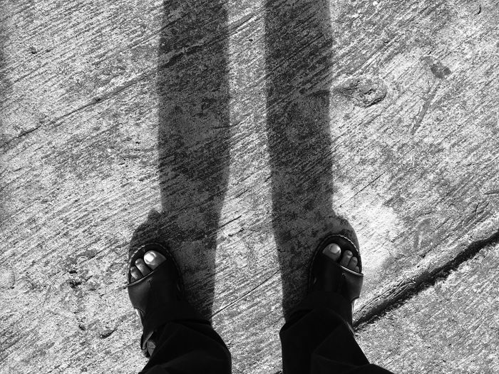 Low section of man standing on concrete path