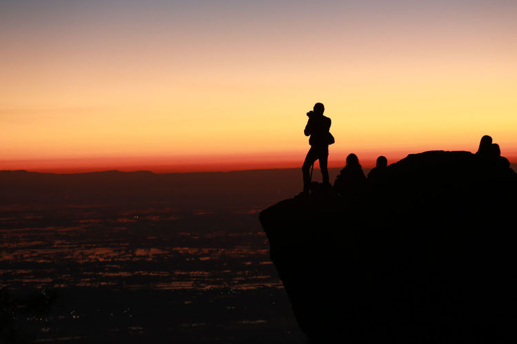 Silhouette people on rock against sky during sunset
