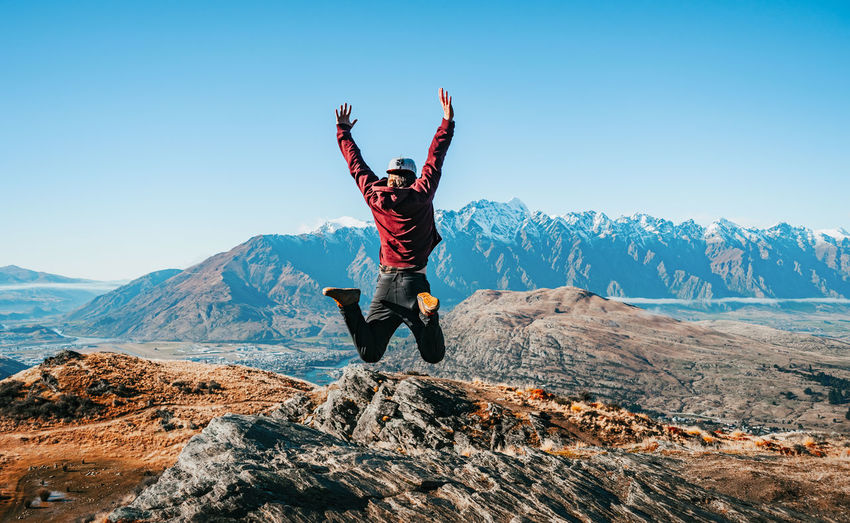 Man with arms raised in mountains against sky