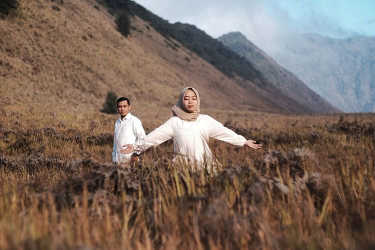 Full length of couple on field against mountains