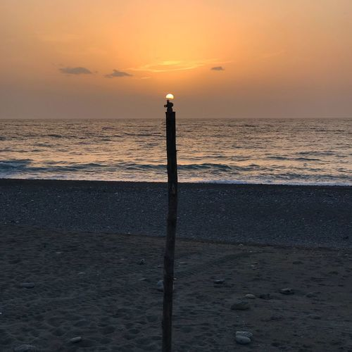 The sunset light at the beach Sea Sunset Horizon Over Water Water Beach Tranquility Beauty In Nature Tranquil Scene Sand Silhouette Wooden Post No People Nature Outdoors Sky