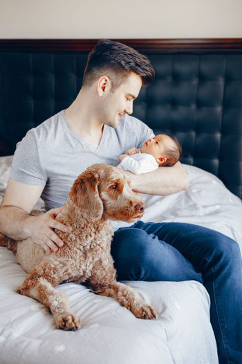 Father carrying baby girl while sitting on bed with dog at home