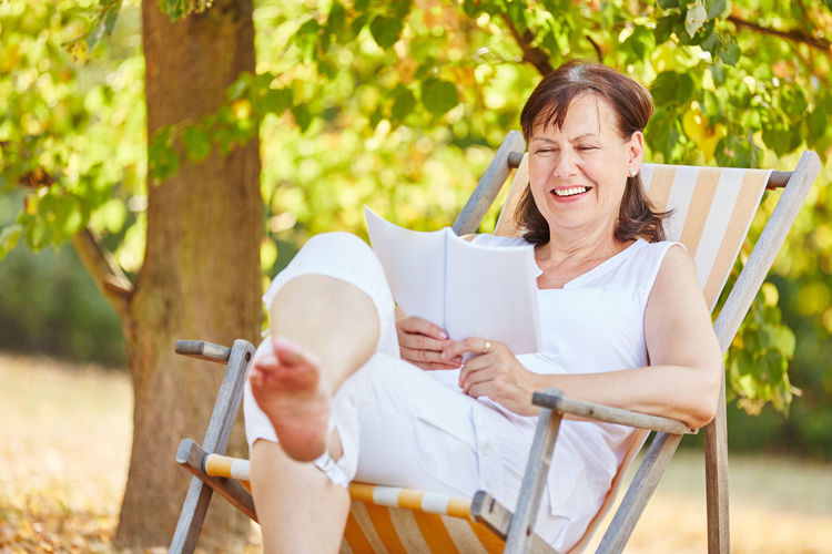 Woman Reading Book While Sitting On Deck Chair At Park