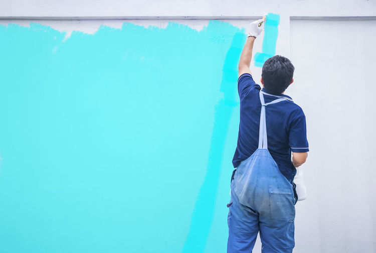 Rear view of painter painting white wall