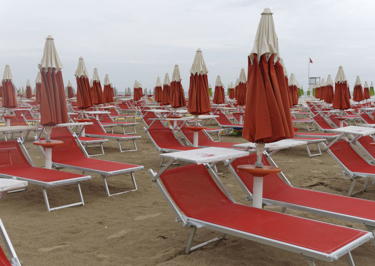empty beach at the end of season, Adriatic sea riviera, Italy, Europe Absence Arrangement Beach Deckchairs Deserted Dreary Emptiness Empty End Of Season  Europe Horizontal Italy No People Nobody Off Season Overcast Parasol Parasols Red Season  Sunbeds Sunshades Tranquility Vacation