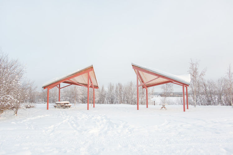 Picnic Tables Under Shed On Snow Covered Field Against Sky