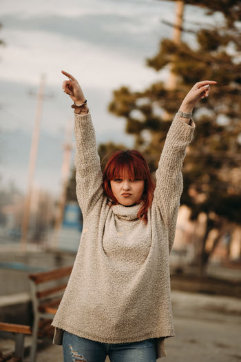 One Person Arms Raised Human Arm Portrait Focus On Foreground Looking At Camera Real People Happiness Casual Clothing Lifestyles Gesturing Women Front View Leisure Activity Waist Up Young Adult Day Clothing Warm Clothing Outdoors Hairstyle Human Limb Hand Raised