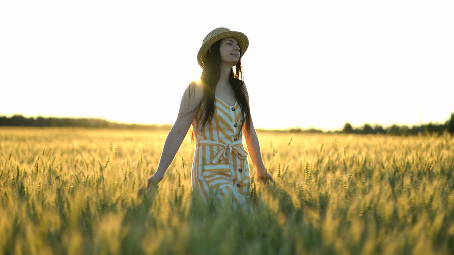 Woman walking in a field with open arms.