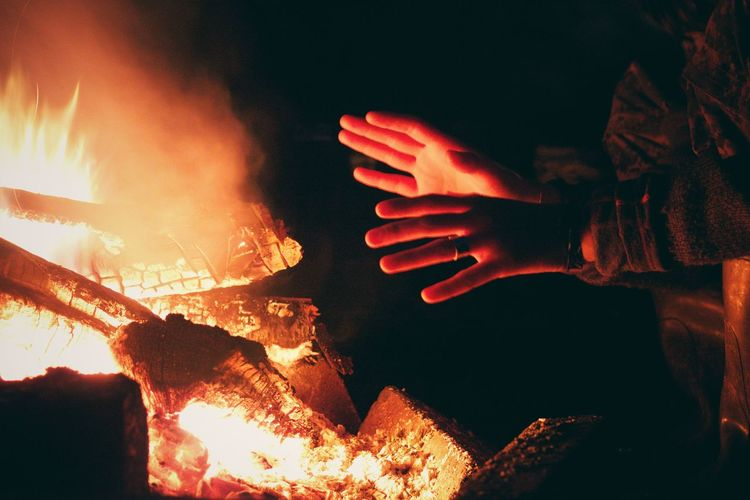 Cropped hands by campfire at night