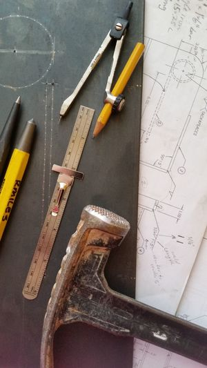 Close-up of hammer with blueprint and work tools on table