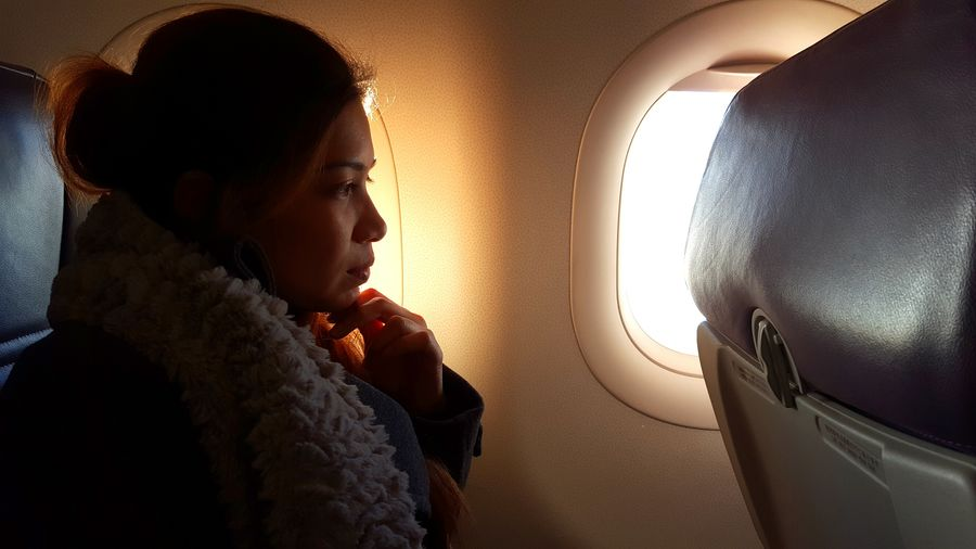Side view of young woman sitting in airplane