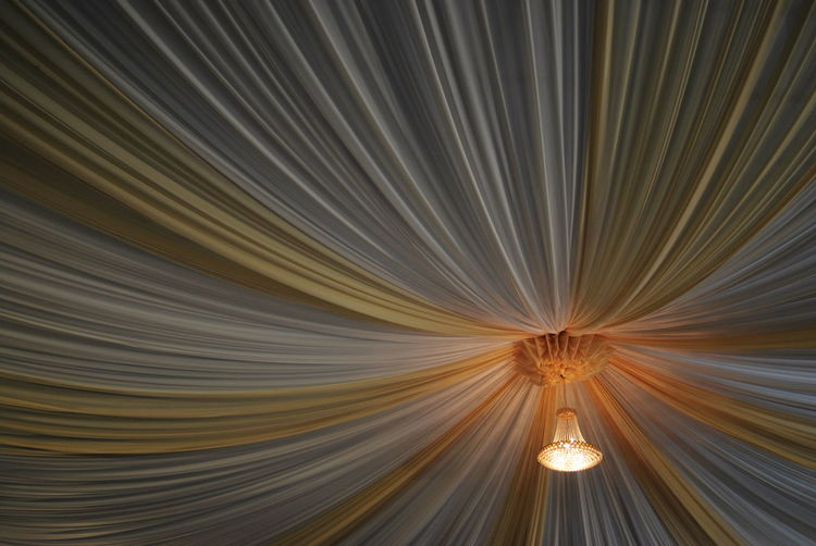 Illuminated chandelier hanging from curtain