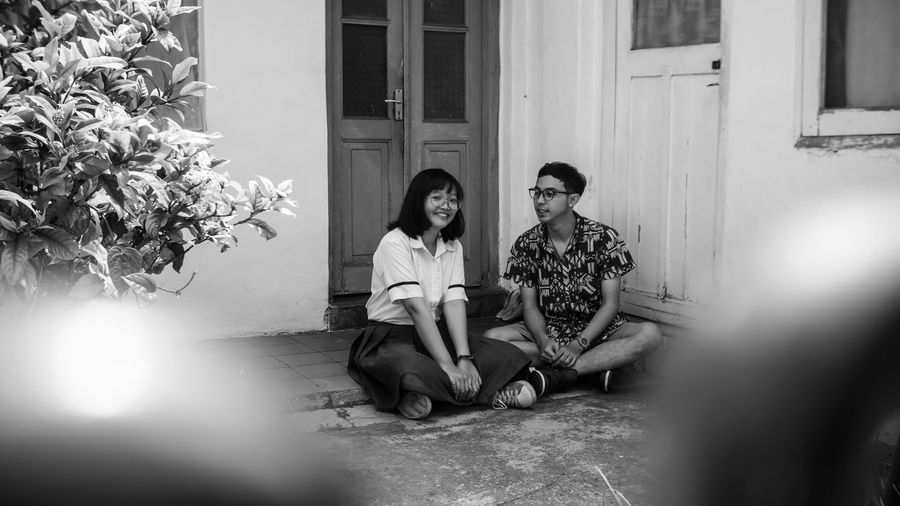Couple talking while sitting in front of house