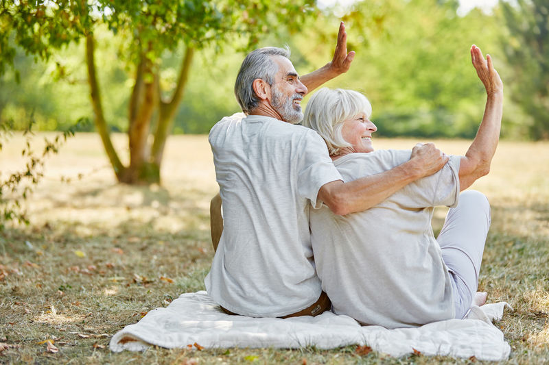 Rear View Of Senior Couple Sitting At Park