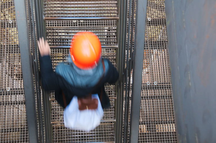 Walking up the stairs Bag Blurry On Purpose Day Grid Hand Handrail  Helmet Industrial Lattice Metal Moving Orange Color Person Stairs Steel Top Perspective Woman