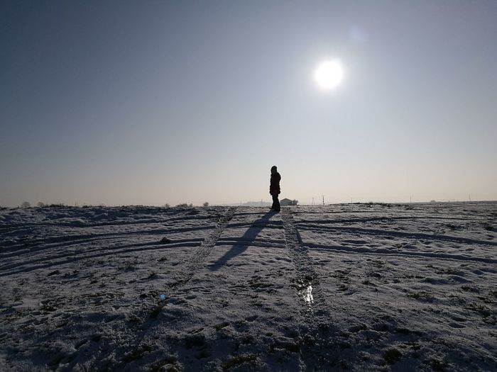 Person Standing On Snow Covered Landscape Against Sky