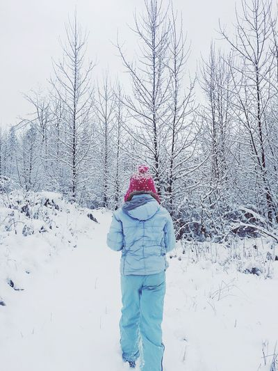 Rear view of person walking on snow in forest against sky