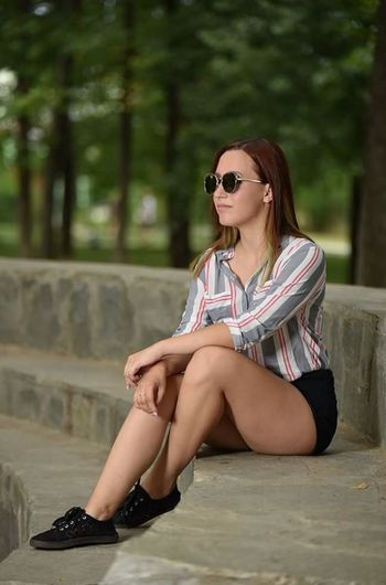 Sitting Sunglasses Only Women One Woman Only Full Length Adults Only One Person Adult One Young Woman Only Summer Long Hair Beautiful Woman Day People Brown Hair Outdoors Sandal Young Adult Vacations Young Women