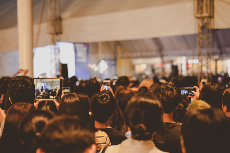 Nightlife and youth activity with backside of crowd in concert hall