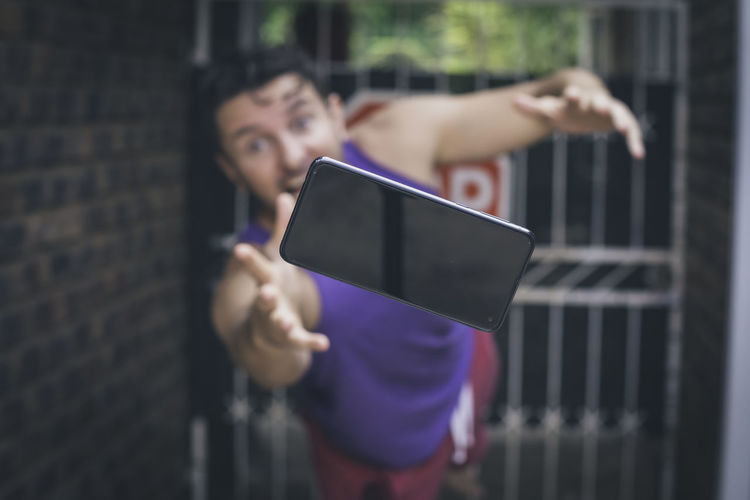 Portrait of man diving for his dropped mobilephone, outdoors.
