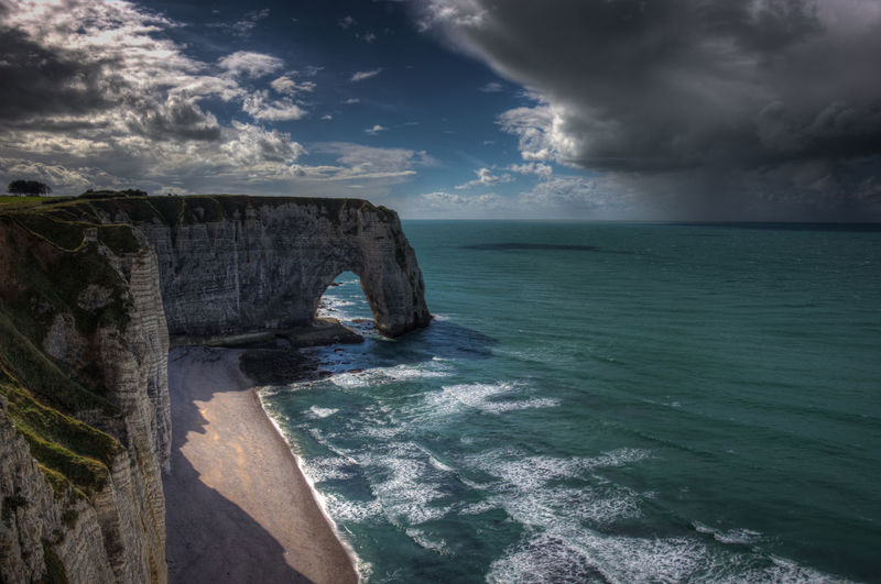 Idyllic shot of rock formation in sea against sky at etretat