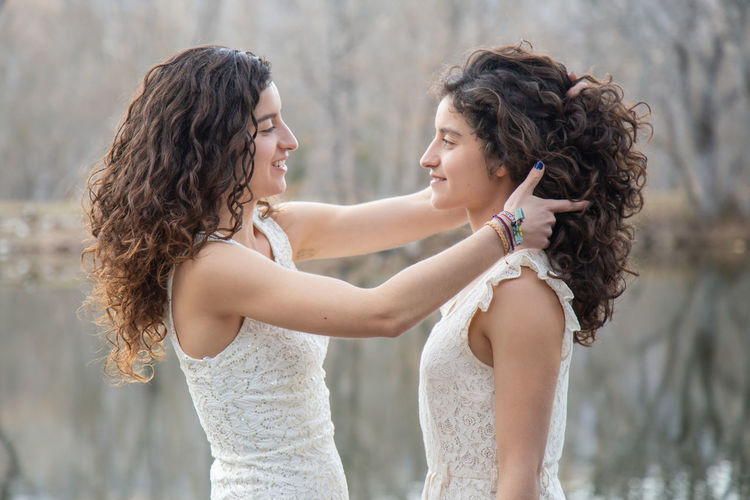 Side view of smiling young woman holding sister hair while standing by lake