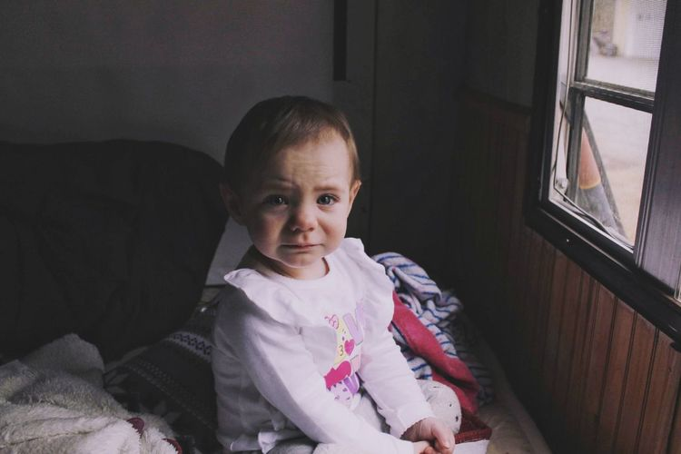 Portrait of cute baby girl crying while sitting on bed at home