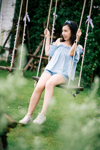 Girl sitting on swing at playground