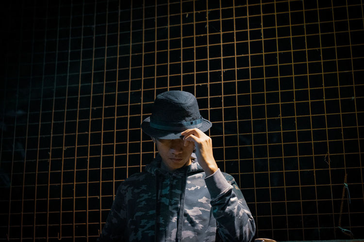 Man in hat standing against fence