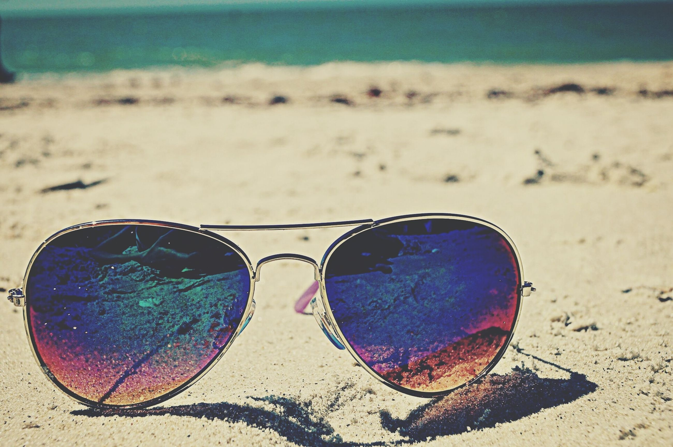 beach, sand, shore, sunglasses, focus on foreground, close-up, day, outdoors, circle, sky, tranquility, nature, sea, sunlight, no people, field, blue, water, transportation, landscape