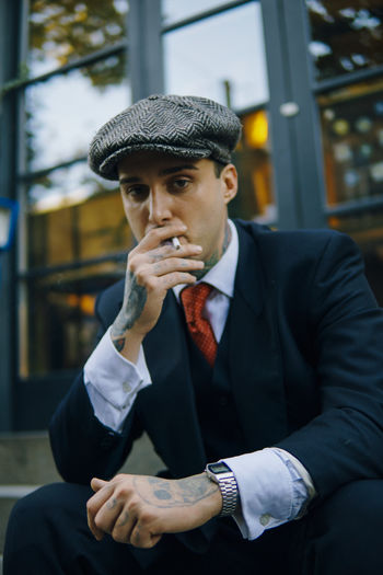 Low angle portrait of young male model smoking cigarette while sitting outdoors