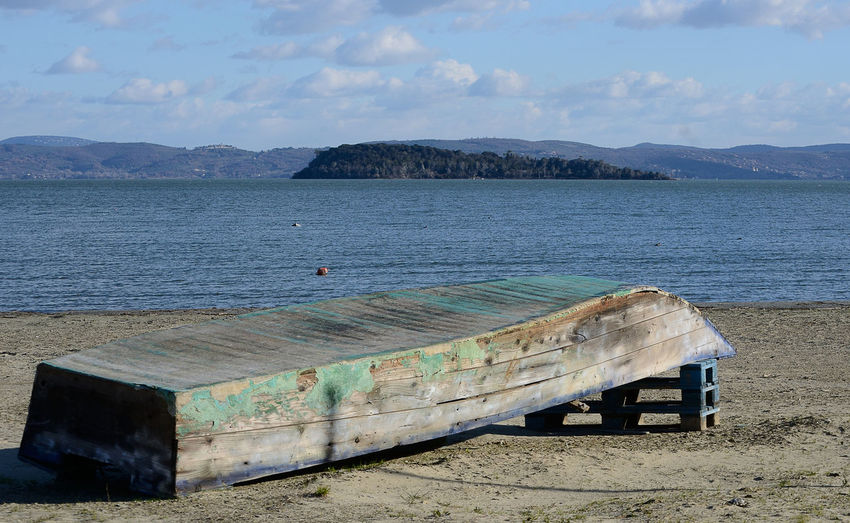 old wooden boat abandoned on the beach of a lake on wintertime Trasimenolake Wintertime Winter Sunny Sunlight Lake View Lake Sky Water EyeEm Nature Lover Boat Abandoned Beauty In Nature Nautical Vessel Outdoors Cloud - Sky Scenics - Nature Tranquility Damaged Island Landscape