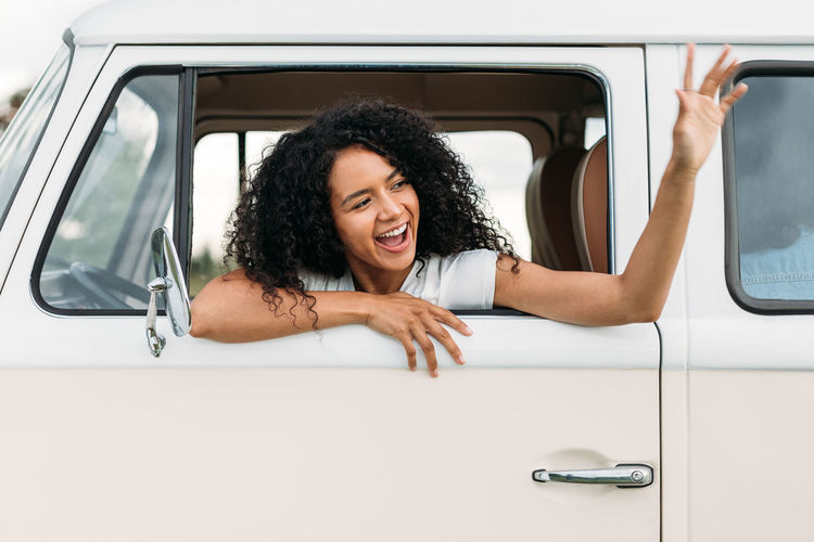 Portrait of happy young woman sitting on car window