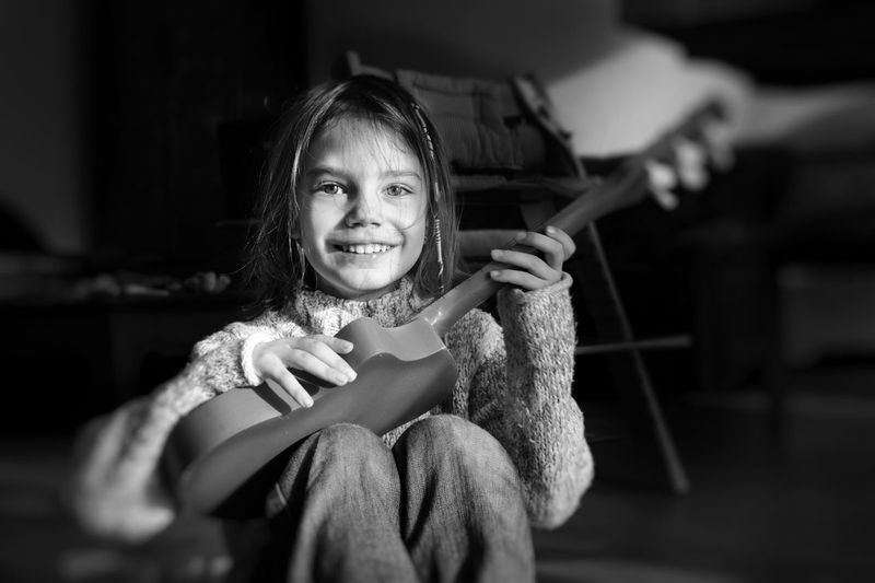 Portrait Of Smiling Girl Playing Guitar