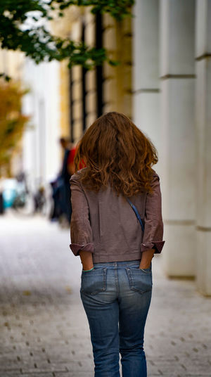 Rear view of woman standing on street
