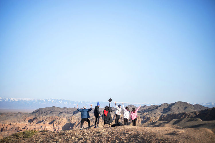 Group of people on mountain against clear sky
