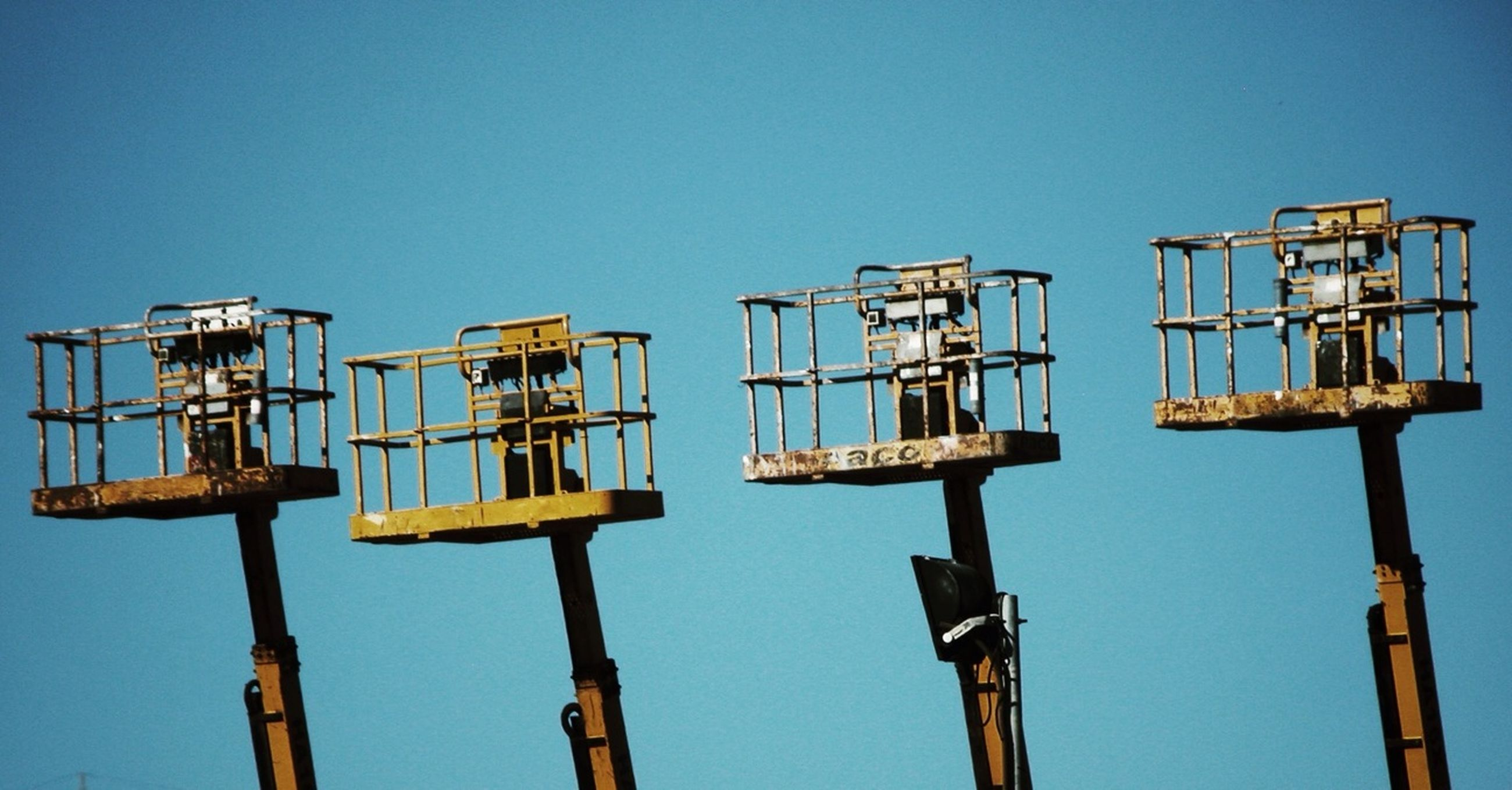 clear sky, low angle view, blue, copy space, pole, industry, fuel and power generation, construction, metal, construction site, technology, lighting equipment, outdoors, day, crane - construction machinery, no people, electricity, equipment, built structure, sunlight